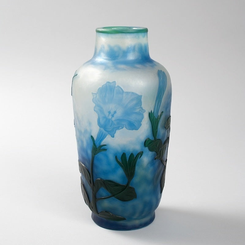 A French Art Nouveau wheel-carved cameo glass vase by Daum, featuring blue flowers and dark green stems and leaves against a mottled white and blue ground. Circa 1900.  A vase decorated in a similar style is pictured in: Daum: Collection du muse
