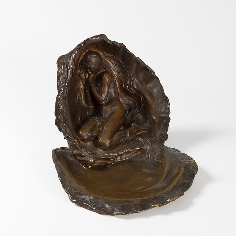 """A French Art Nouveau patinated bronze figural sculpture, entitled """"La Perle,"""" of a female nude nestled within an oyster shell by Max Blondat, circa 1899.   An identical dish was exhibited at La Société des Artisties Français in 1899 (see The"""