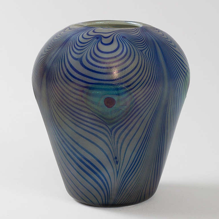 A Tiffany Studios New York Favrile glass peacock vase with iridescent pulled decoration stylized to look like peacock feathers by Louis Comfort Tiffany. The peacock feather was a favorite motif of Louis Comfort Tiffany, circa 1900.   Signed,