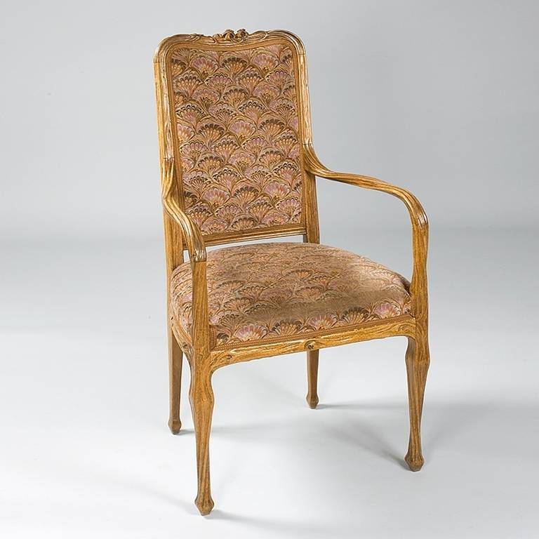 A French Art Nouveau walnut armchair by Louis Majorelle, featuring sinuously curved arms and legs. The top of the chair is decorated with an intricately carved floral motif. It is upholstered in a feather-like pattern fabric in grey, rust and