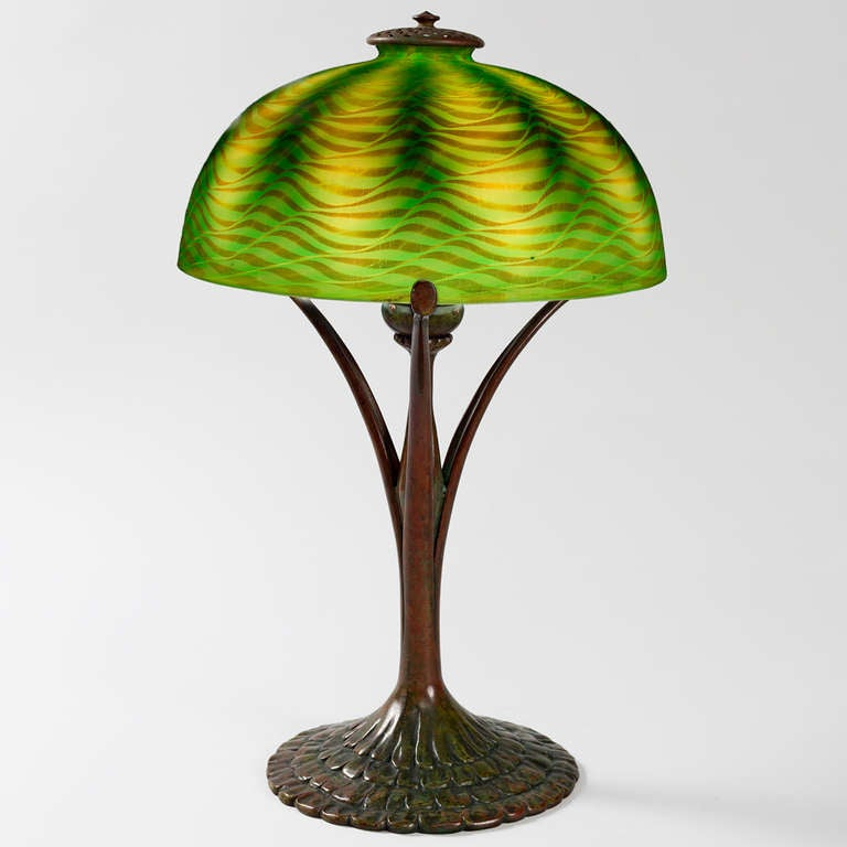 "A Tiffany Studios New York Favrile glass and patinated bronze table lamp, featuring an iridescent green ""Damascene"" shade atop a patinated bronze ""Ruffle"" base. 