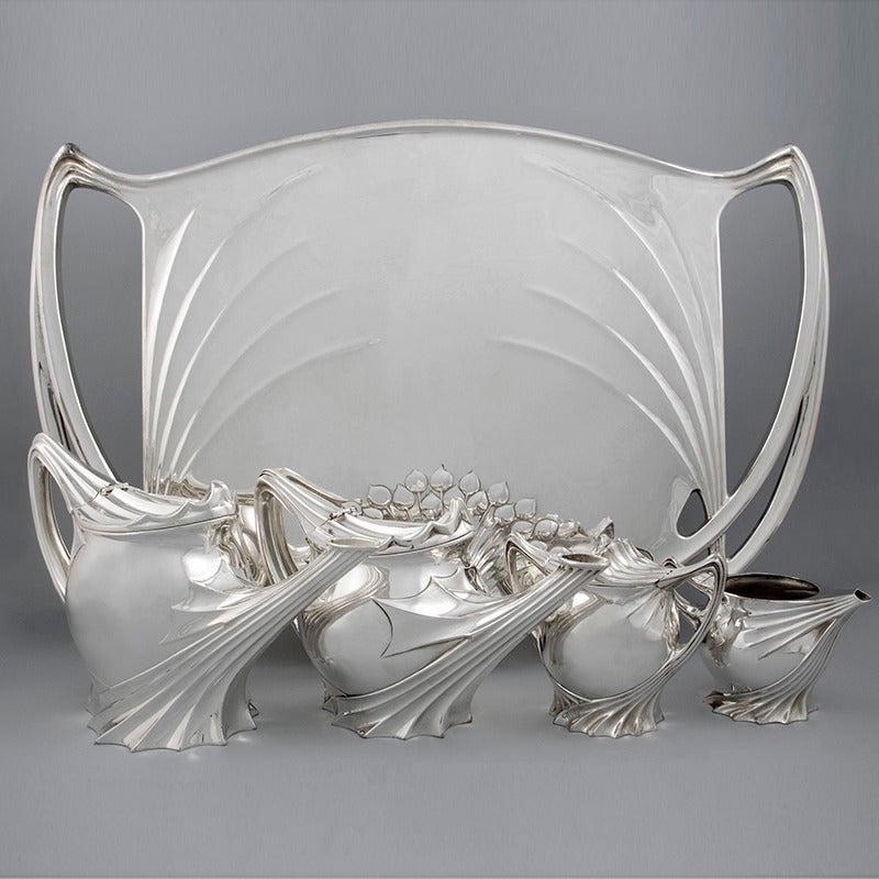 A rare and important French Art Nouveau silvered metal coffee and tea service by Paul Follot. The set includes a tray, a tea and a coffee pot, and containers for sugar and cream. The set is decorated with whiplash curves, fabric-like folds and a