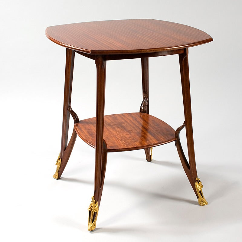 A French Art Nouveau mahogany two-tiered square table by Louis Majorelle, featuring featuring a detailed border on the top tier and bronze sabots on the legs, circa 1900.   A similar table is pictured in Majorelle - Nancy: décorations