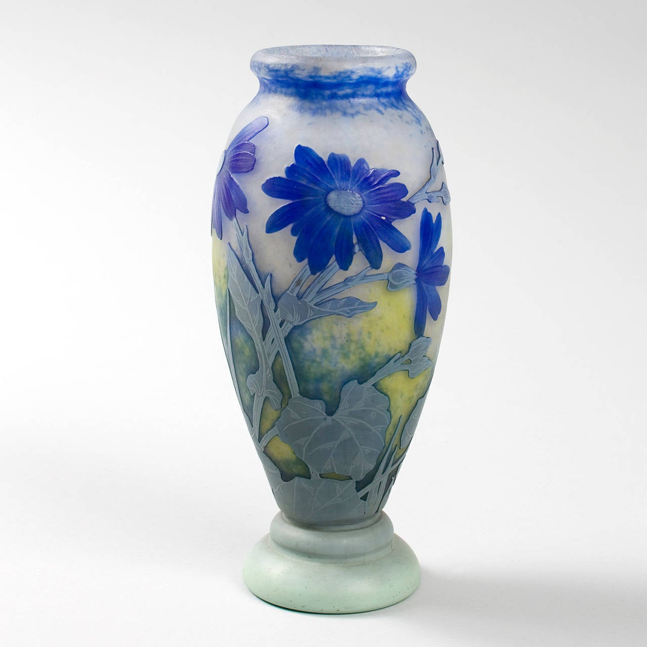 A French Art Nouveau wheel-carved cameo glass vase by Daum, featuring a decoration of blue flowers and light blue and grey stems and leaves on an opaque, mottled white and yellow ground, circa 1910.