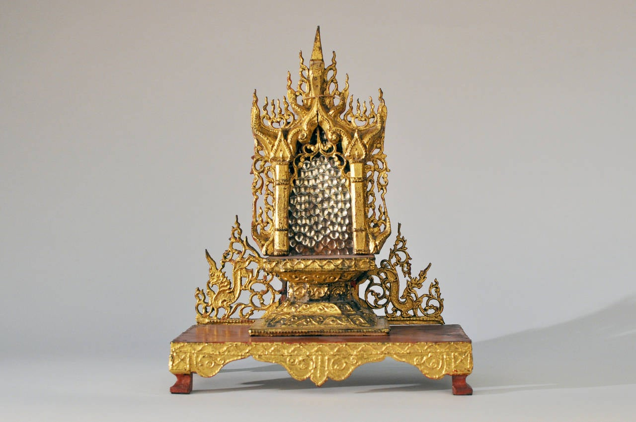 This exceptionally detailed Burmese Buddha shrine dates to the 19th century. Originally used to hold a sacred bronze Buddha figure, it is beautiful work of art on its own. The base is teakwood and it has been covered in red lacquered genuine