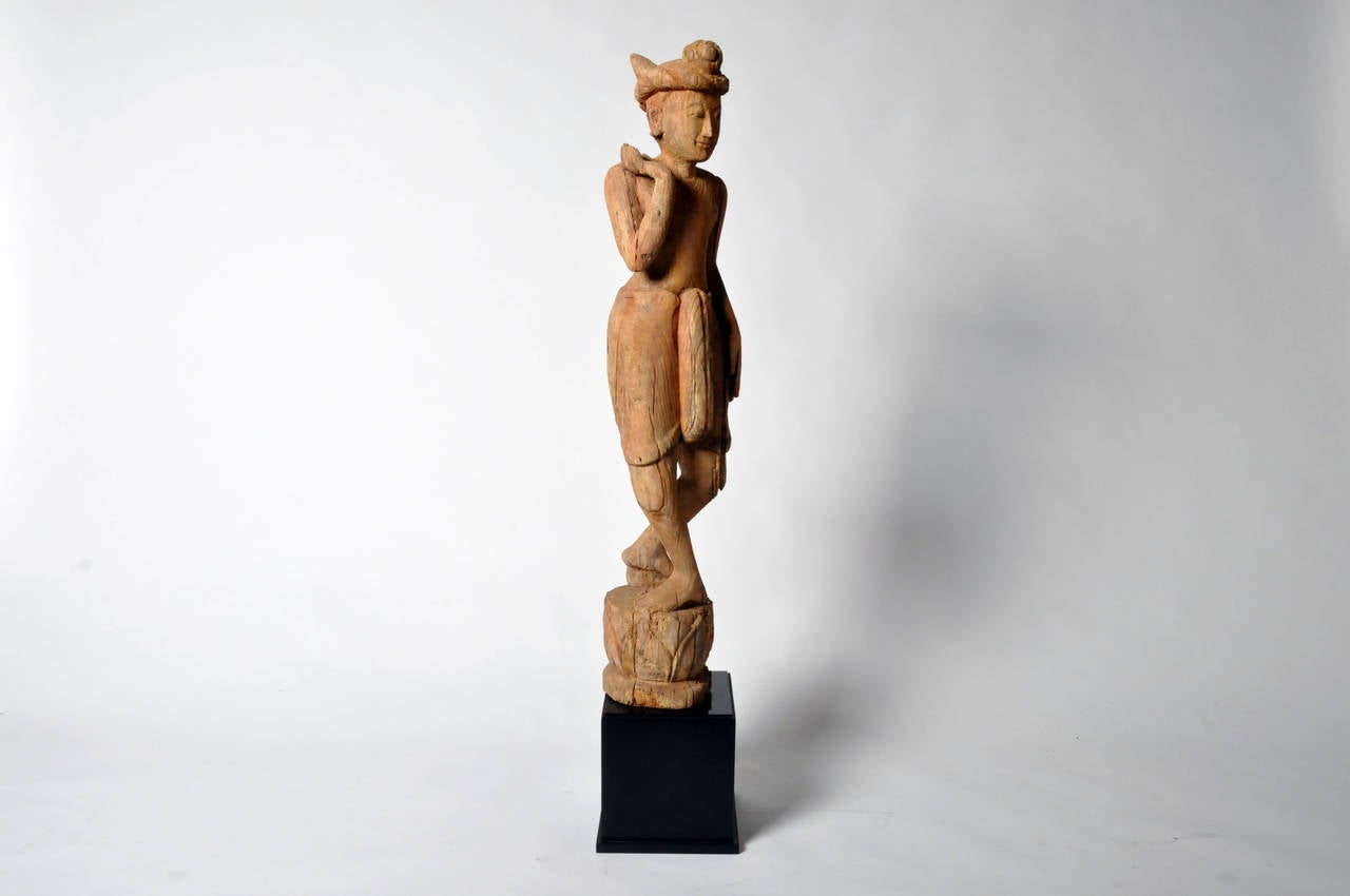 This sculpture is from Thailand and made from teak wood, circa 1980. It is depicting a gong-carrying figure, standing on a lotus form base and raised on a black wood pedestal.