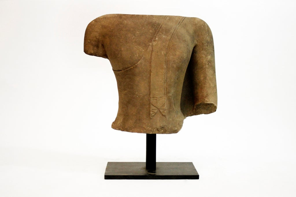 This sizeable torso is from Ayutthaya, and is one of three pieces that made up a figural sculpture of Buddha. Comprised of elegant curves and soft lines, the details of diaphanous robes draped over the left shoulder are still intact. Given the