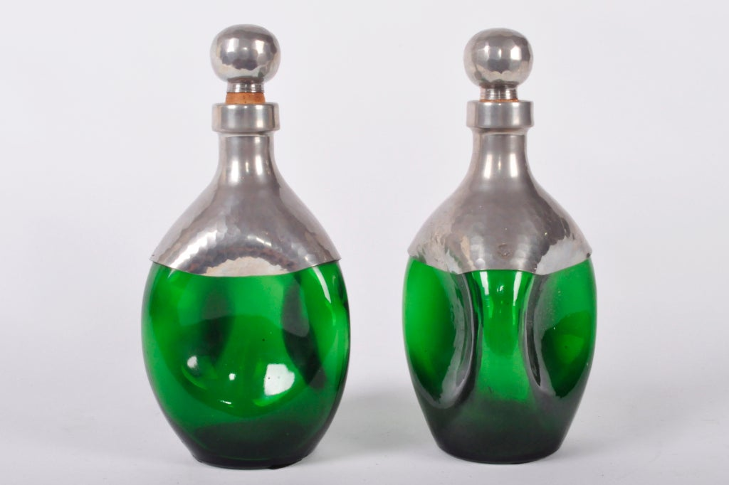 These French green glass vessels are accented with hammered pewter and cork tops.