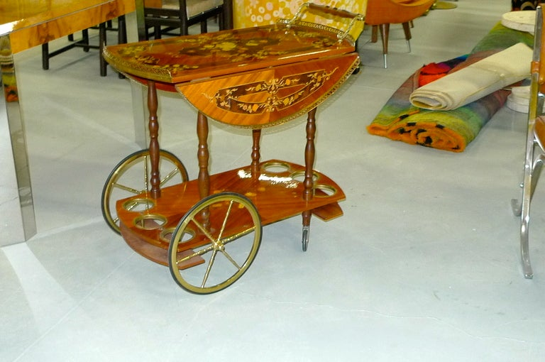 1960's Italian bar cart or tea trolley by Sorrento with elaborate inlaid marquetry on herringbone veneer which has a high gloss clear coat.  The side wings can be latched up to create a large round circular serving tray, or hang freely from their