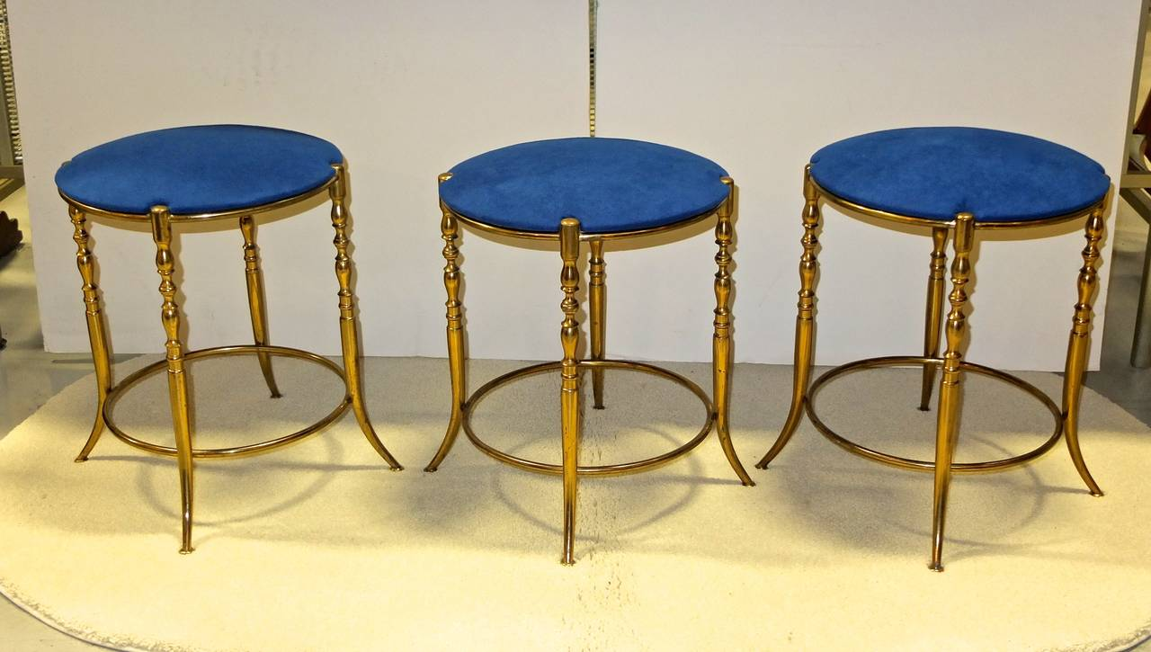 Extremely rare set of three round brass Chiavari stools, made in Italy, circa 1960. Four legs with flared tapered legs around an upper and lower brass ring. Fitted round seat upholstered in royal blue suede.  Produced by F.lli Levaggi in the