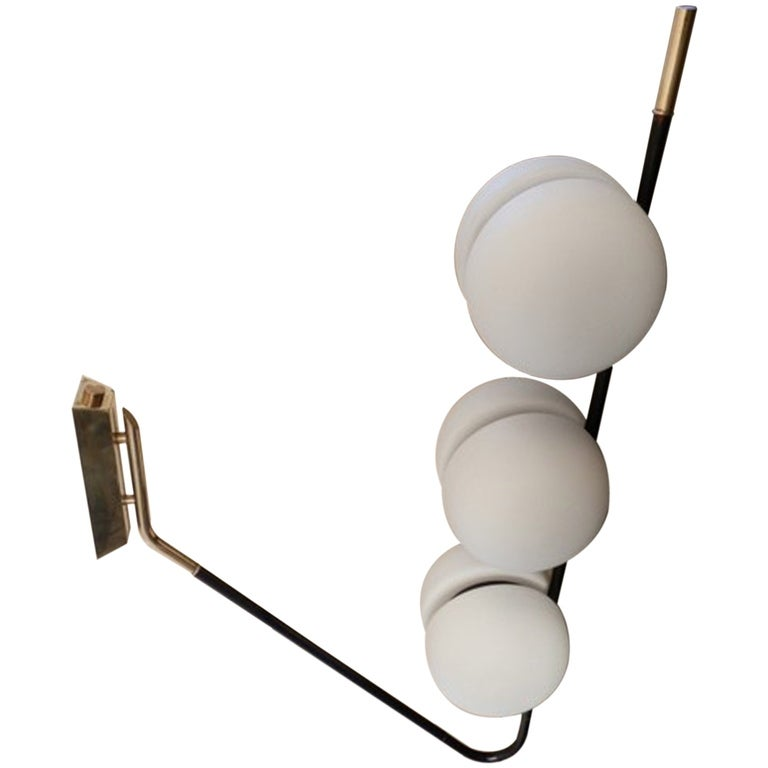 This large scale unusual French modernist fixture can be mounted either to a wall or ceiling and can be positioned pointed in either direction.  The elbow form enameled steel arm with brass fittings extends from a substantial rectangular brass
