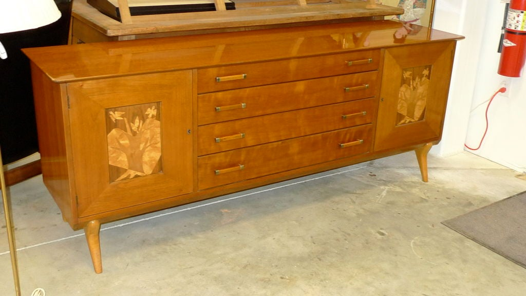 A handsome sideboard or buffet cabinet with two doors with marquetry inlay and four drawers.  Splayed tapered legs add to the Italian stylings.