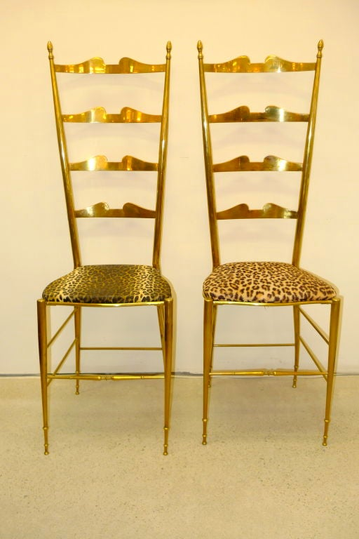 Pair of brass Chiavari ladder back chairs with nearly matching leopard vinyl seat covering.