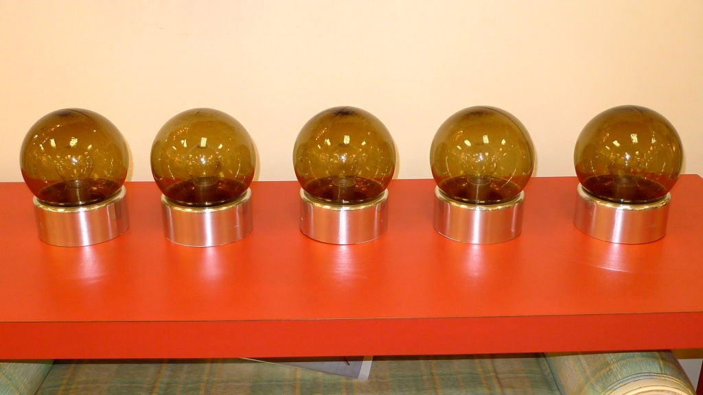 Totally groovy ceiling or wall lights produced by Lightolier in the early 1970's.  Smoked brownish glass ball chade on polished aluminum round bases.<br /> <br /> Price is for the set of 5 or $500 each.