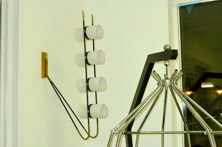 This French 1950's 8 bulb lamp is of extraordinary construction and versatility allowing it to mounted either as a wall lamp or ceiling fixture.  Matte black steel parallel arms bent like an elbow supporting four double sets of cylinder shaped