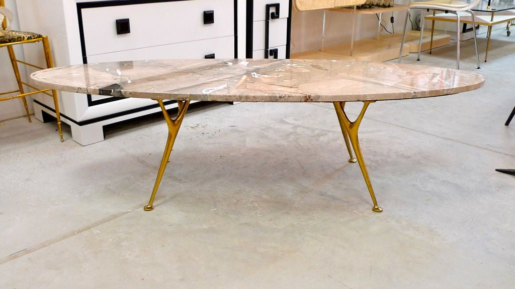 An exceptional 1950s Italian coffee table consisting of an long oval 'surfboard' shaped marble top supported by sinewy organic Y-form cast solid bronze legs polished to a mirror finish.