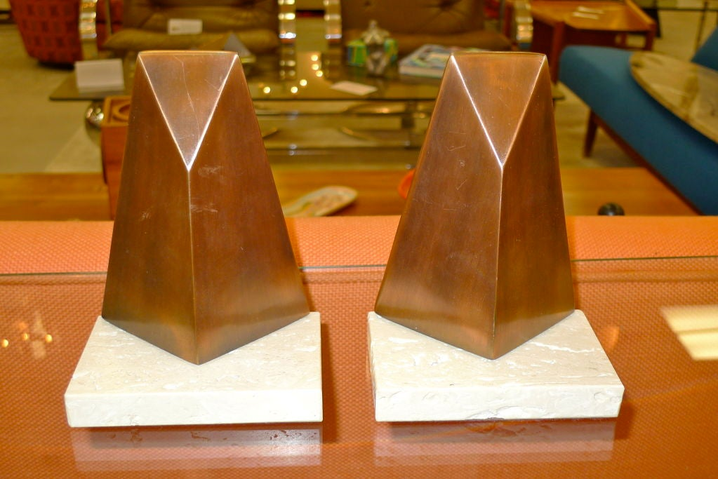 Sculptural bronzed metal bookends by William Macowski for Ketcham & McDougall, 1972.  Abstract pyramidal form mounted to travertine base.