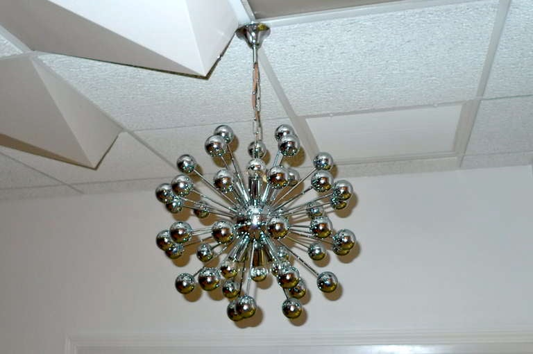 1970's chrome Sputnik sphere chandelier. Chrome balls on chromed metal rods fitted into a chromed central sphere out of which emanate six candelabra size bulb sockets - 3 pointed up and 3 pointed downwards.  Shown here with chromed top round