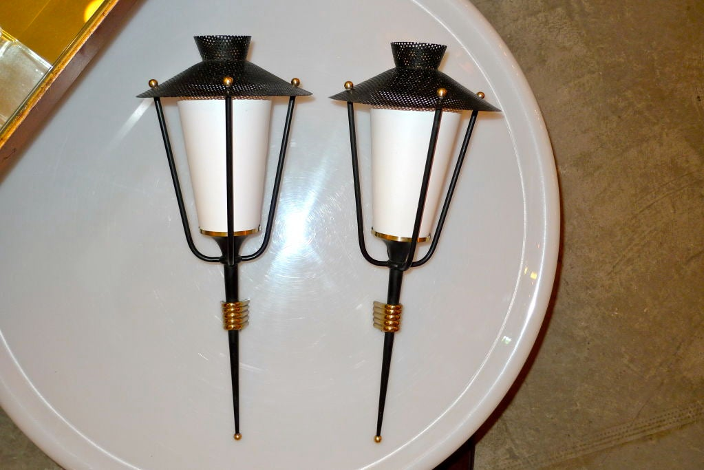 A matching pair of French 1950's tochere lantern sconces produced by Arlus, design attributed to Mathiue Mategot.  Matte black enamel and polished brass wall mounts.