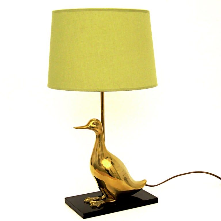 Chic and charming table lamp consisting of a brass duck figure on a lacquered wood rectangular base.  Attributed to Sarreid of Spain. Brass has been clear lacquered to prevent tarnishing.