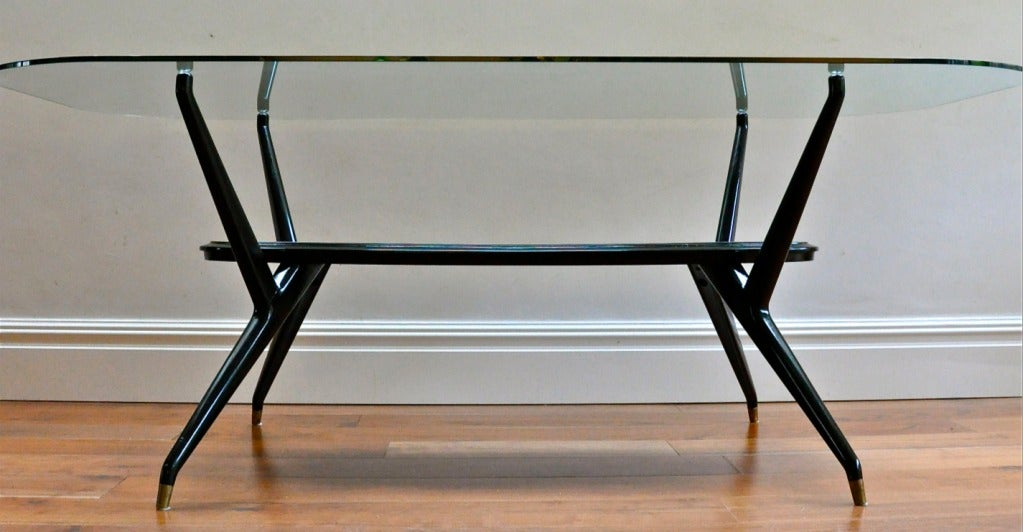 Magnificently sculptural 1950's Italian dining table in black lacquered wood with brass capped feet, in the style of Ico Parisi and Carlo Mollino. Glass top shown for display only. We recommend a boat shaped glass top 42