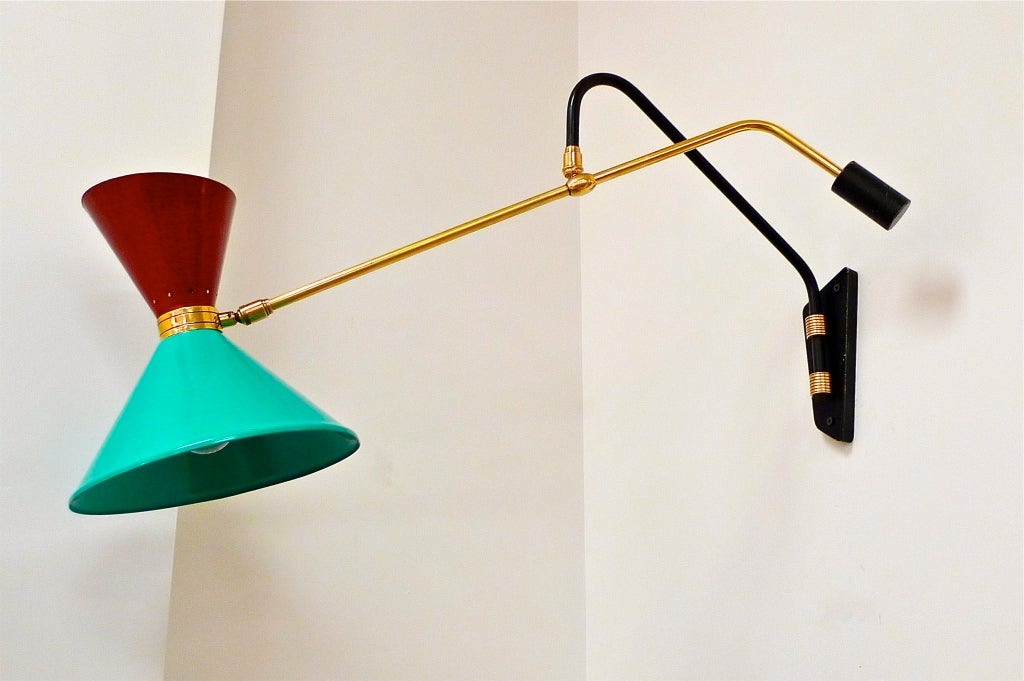 Joyful and intricately constructed wall mounted balancing swing arm lamp by Pierre Guariche with tu-tone diabolo shade in enameled aluminum. Rewired and sockets changed to accept screw cap bulbs (full size in bottom, candelabra bulb in top cone.