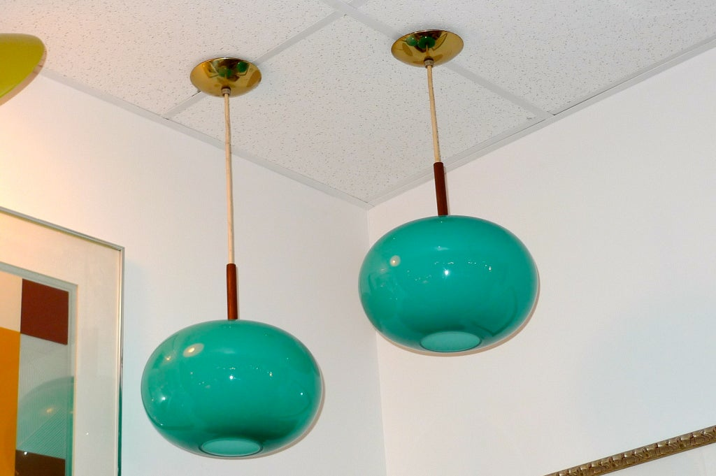 Pair of turquoise or seafoam colored glass pendants in shape of oblate spheroid by Prescolite of California.  Each hangs from vinyl coated wire and has a dark wood stem (possibly walnut or teak) and original brass ceiling caps (5.5