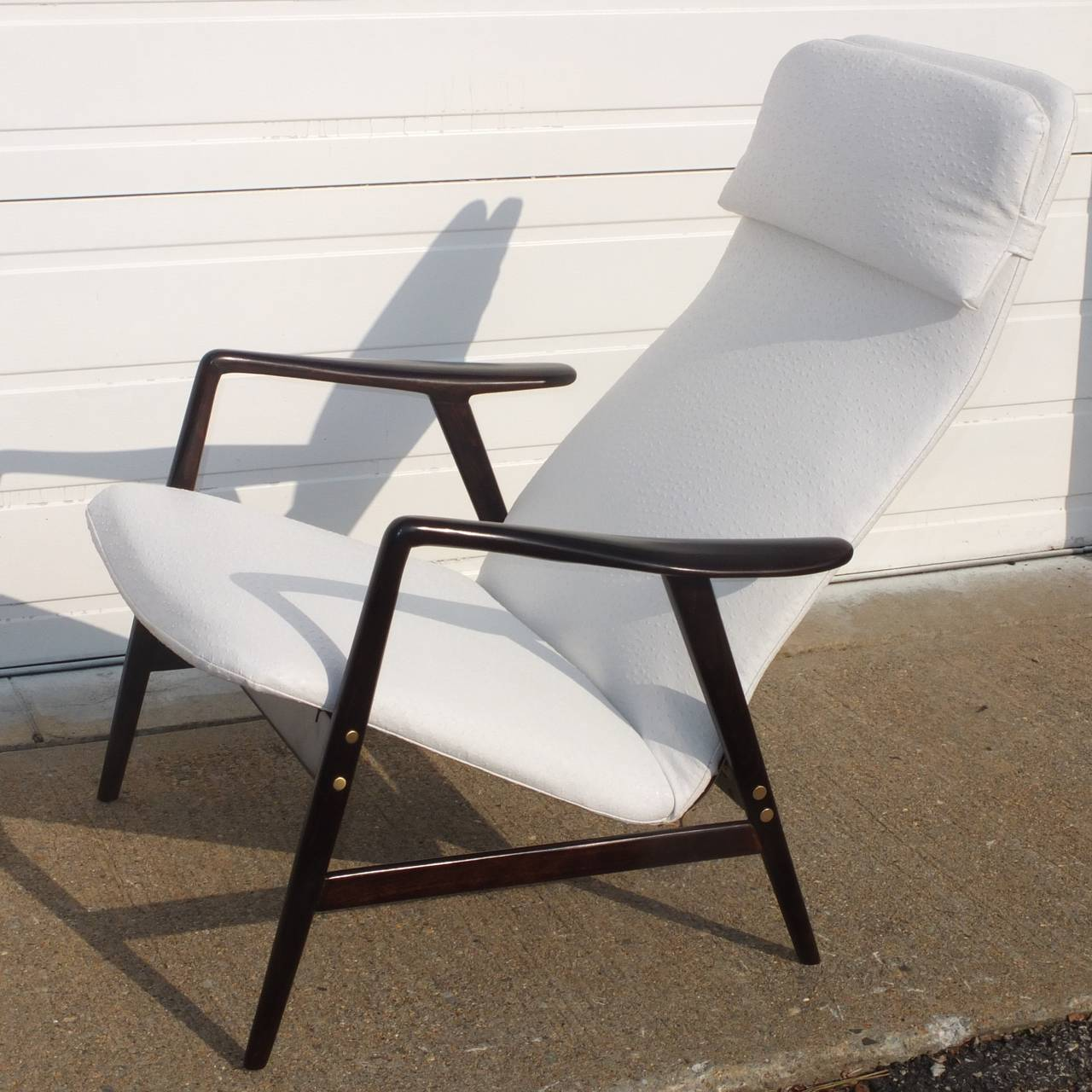 "Gorgeous adjustable ""Kontour"" lounge chair by Alf Svennson for Fritz Hansen, Denmark 1957.  Beech wood frame with sculptural armrests, stained black and polished to high sheen. Re-upholstered in faux white emu. Has two reclining"