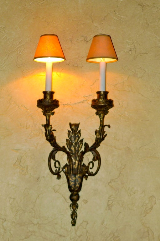 An outstanding set of 8 stately Italian gilt metal and wrought iron sconces with acanthus leaves and scalloped edged bobeches on its double branch arms.  These sconces have been together in the same Boston estate since the 19th century.