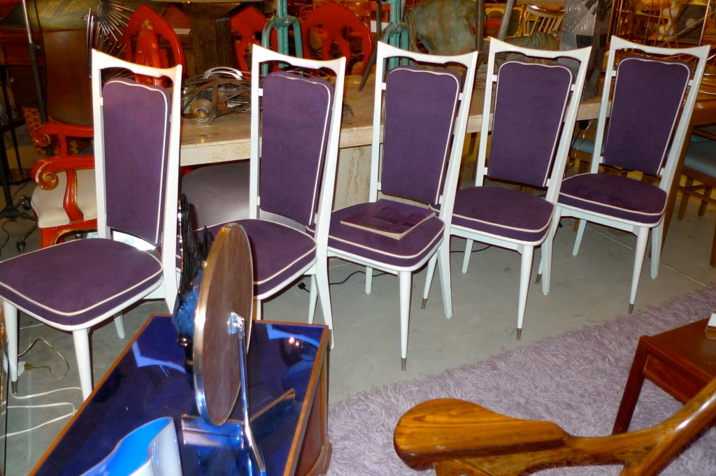 Set of six French dining chairs from the late 1940's/early 1950's with modernist open floating back rest.  White lacquered solid wood and steel sabots.  Newly upholstered in purple micro suede with contrasting white piping.