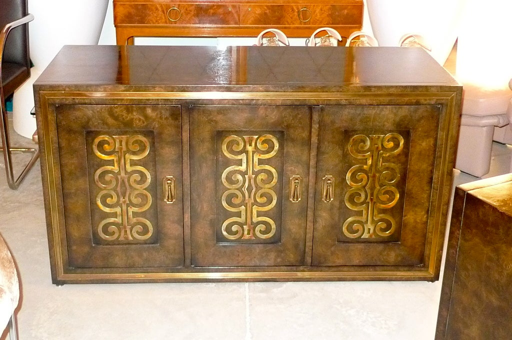 Mastercraft cabinet of drawers made from beautifully polished Carpathian elm with decorative brass appliques on three doors and brass trim around the outer edges.  The door on the left opens to an open cupboard space with a single removable shelf on