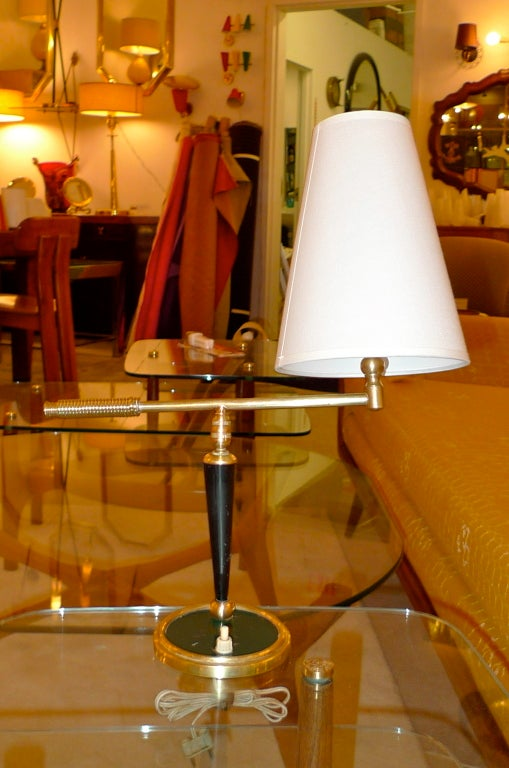 Handsomely crafted French 1950's table lamp with a an articulating arm on a machine milled swivel joint with brass coil wrapped handle on the arm and a conical white uno shade