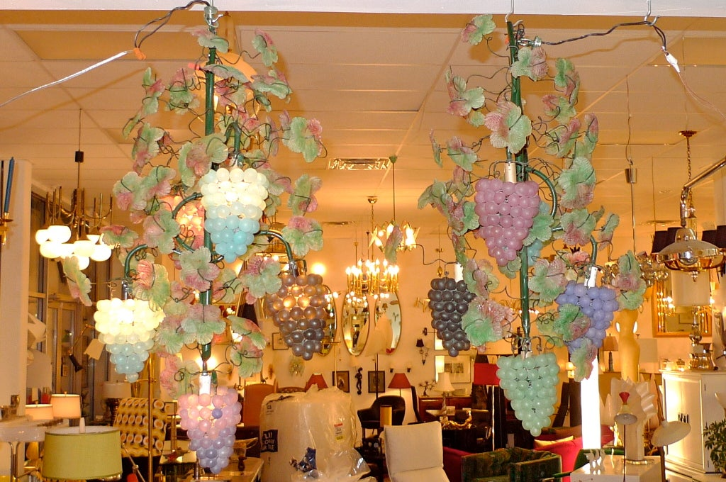 A magical pair of Italian painted iron chandeliers in the form of grape vines with handmade colored glass grapes and leaves.  From the famous old restaurant in Boston's North End, Joe Tecce's. Every nook and cranny of Tecce's was decorated like a