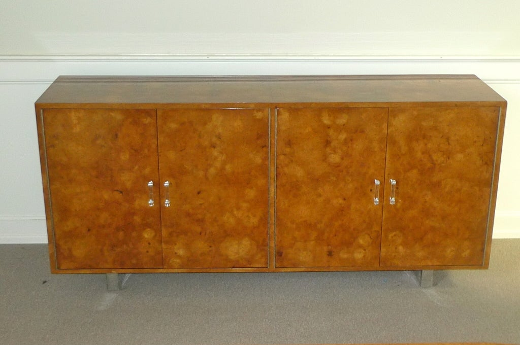 Exotic burl wood credenza or buffet designed by Ernest C. Masi for the French & English Furniture Company of New York.  Probably made in Colombia, South America.  Four doors open to shelves and drawers inside black finished interior.  Pair of chrome