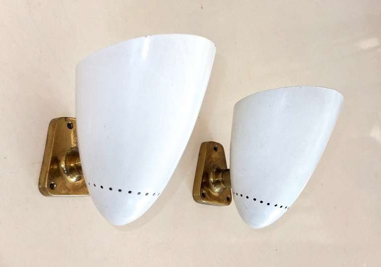 Parabolic aluminum bullet cones with perforated detail and white enamel on a substantial cast bronze pivoting (side to side) bracket by Günter Trieschmann of Stuttgart, circa 1952.  Can be oriented up or down.  Documented: Modern lighting of 50 -
