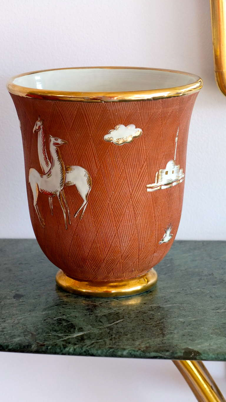 1930's Italian Art Deco vase in the manner of Gio Ponti for Richard Ginori.  Gilt edged mouth and base, hash mark etched terra cotta clay with white glazed enamel floating images suggesting scenes of North Africa....probably Libya which was an