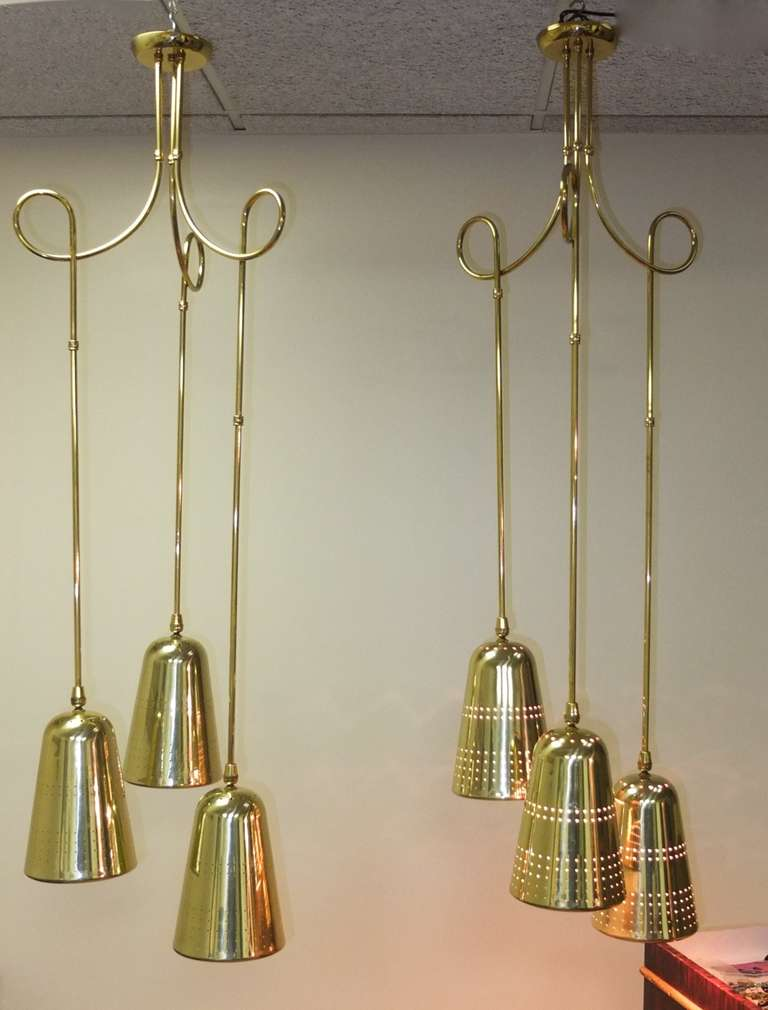 Pair of suspension light fixtures consisting of three perforated brass cones by John C. Virden Lighting Company circa 1955 in the style of Paavo Tynell.  The brass tubing is in sections so can be adjusted and customized .  Even the scrolling loops
