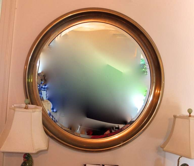 Oversize vintage 1970's porthole mirror by Mastercraft in a wide rimmed solid brass frame around a circular beveled mirror.