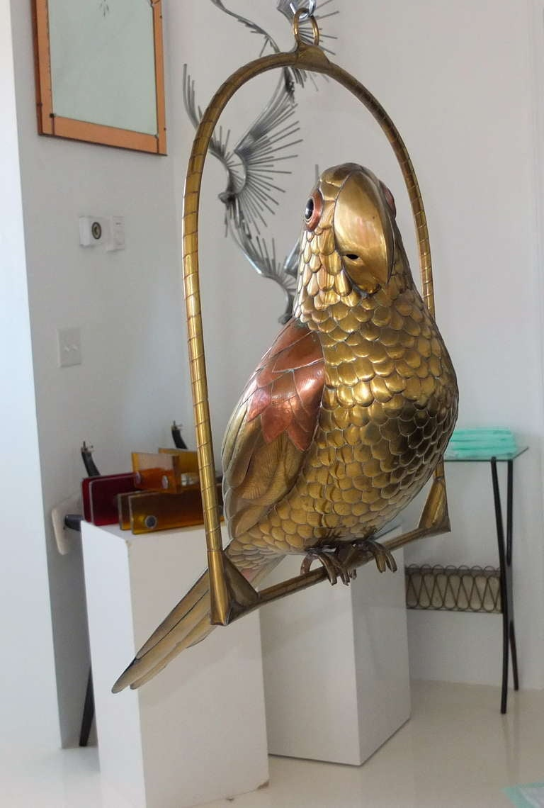 Large brass hand made limited edition perched parrot in swing by Mexican artist, Sergio Bustamante, circa 1970.  See our separate listing for a similarly large parrot as well as a small parrot and small toucan.
