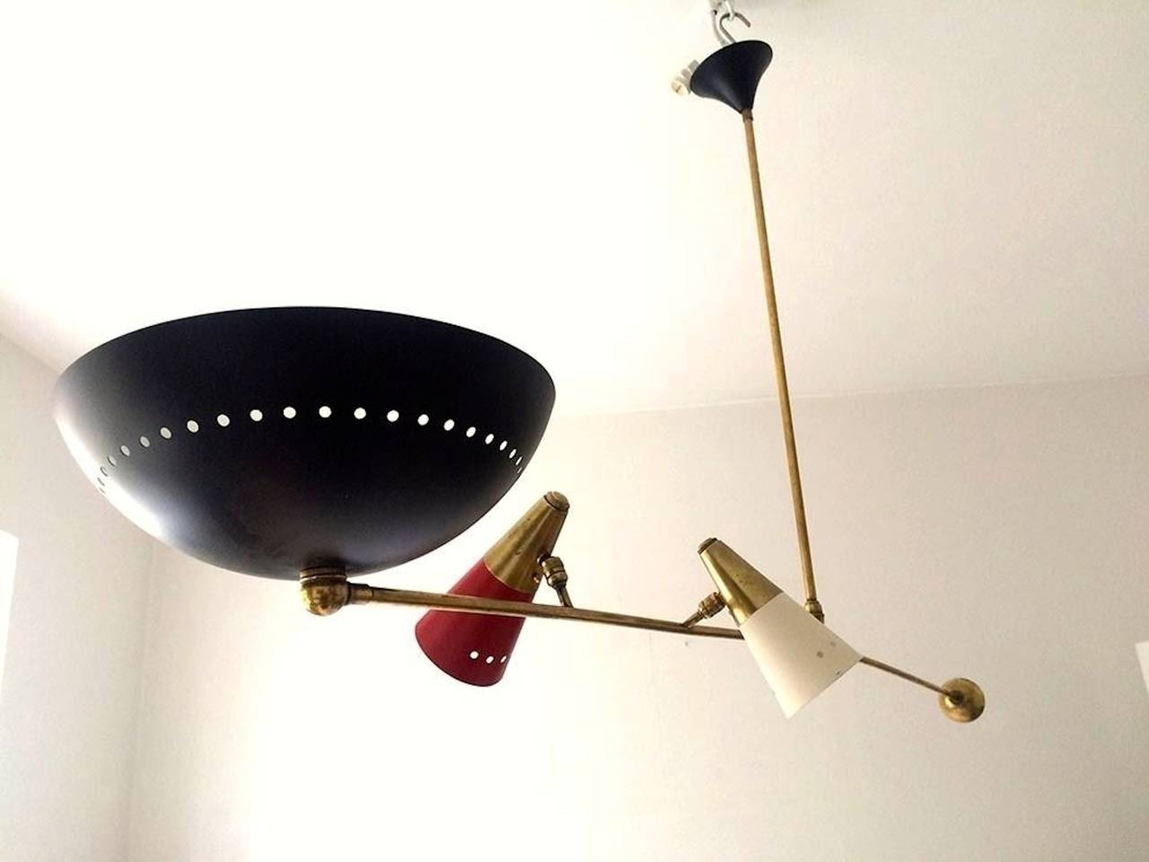 Minimalist and linear pivoting counter-balance pendant light one large black enameled dish reflector which faces up or down plus two articulating cones with brass caps and enameled white and red. Ceiling canopy enameled black. In the style of Angelo