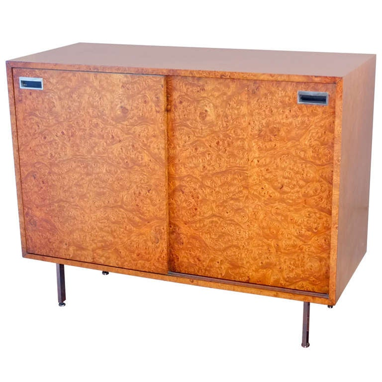 Sublimely chic gentleman's dressing cabinet by Harvey Probber. Olive burl rectangular case with double sliding doors on stunning polished aluminum legs with round levelers. Sliding doors have inset chrome handles with black enamel. Behind each door