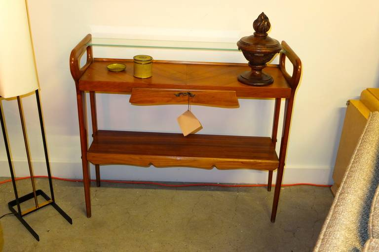 1950's Italian console table in the manner of Ico & Luisa Parisi. A glass insert shelf over two fruitwood shelves with a single drawer, all joined by the shaped open sides, characteristic of the period.