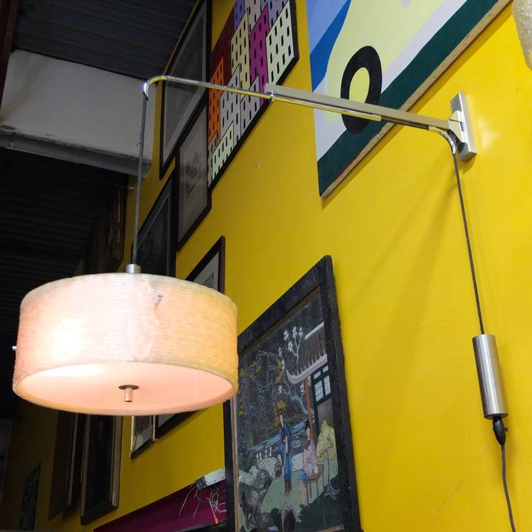 1950's French wall mounted swing arm lamp with counterbalance pulley mechanism for raising and lowering the shade.  The arm swings 170 degrees. In excellent original condition.  Shade is woven plexi with an acrylic reflector.  Fittings are brass