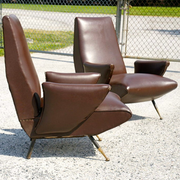 Late 1950's Italian lounge chairs by Nino Zoncada for Framar with steel legs and brass feet tips in original brown skai upholstery.  Giovanni
