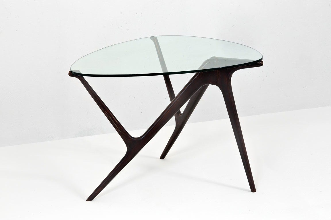 1950s Italian modernist three leg table made of mahogany stained beechwood and an asymmetric glass top which is roughly the shape of a heart or a guitar pick. Two insect-like arms reach out from an organic joint in the two back legs and with dainty
