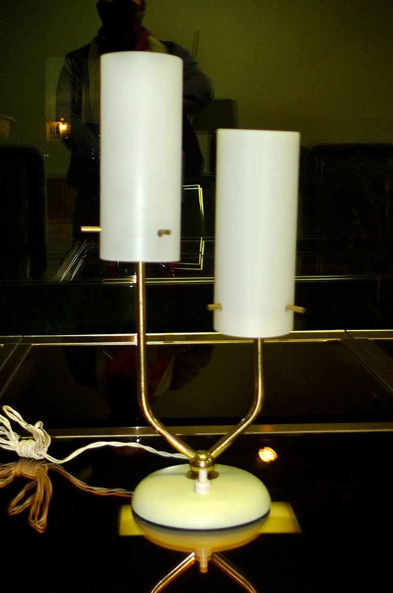 Smart looking table or boudoir lamp by Stilnovo with opaline glass cylinder shades supported by 3 brass pins.