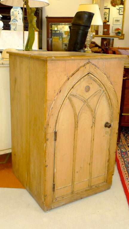 Rustic antique knotted pine cabinet having a single arch shaped door with gothic moldings and plank case construction with a single fixed interior shelf. The arched door appears as though it may date from even earlier than the case itself, possibly
