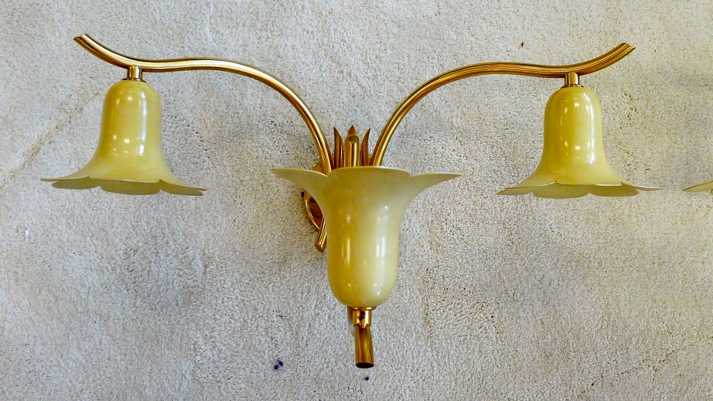 We have two pair of these 1950s Italian three-light sconces in the manner of Angelo Lelii for Arredoluce.