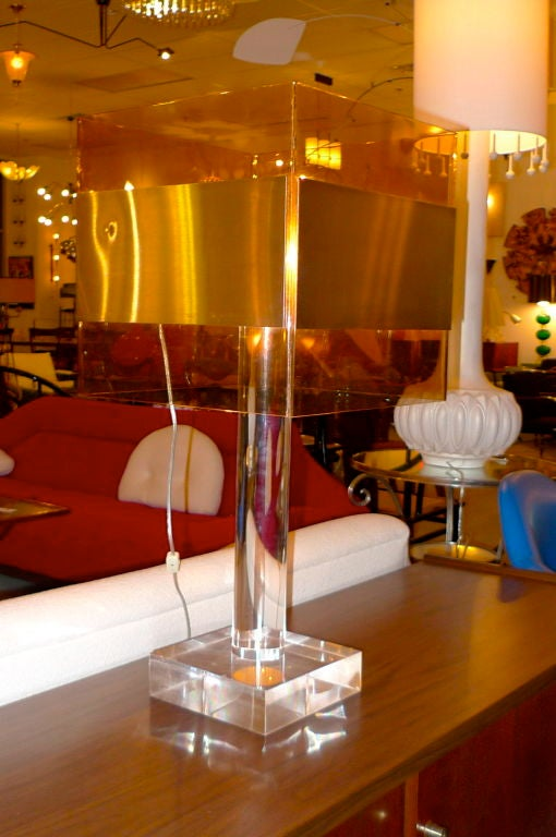A large modernist lamp. Thick clear lucite base and column support a square smoked Lucite shade with applied brushed aluminum banding. Uses 4 small bulbs.