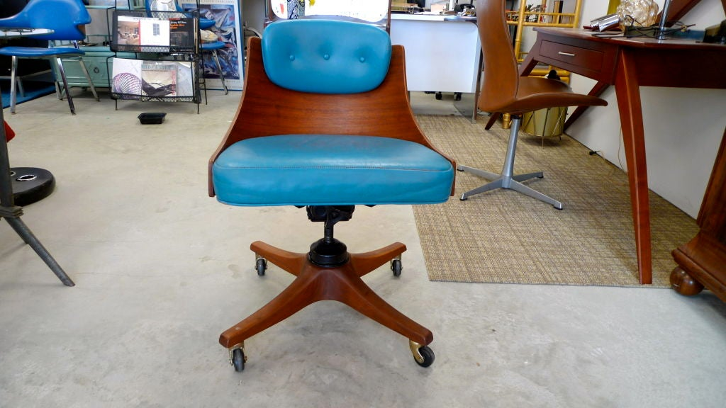Solid walnut four star base on Kilian casters, molded marine-grade plywood with outer walnut veneer barrel-back chair with teal blue leatherette seat and hinged back cushion. Dimensions provided are of chair at nearly its highest setting.  Can be